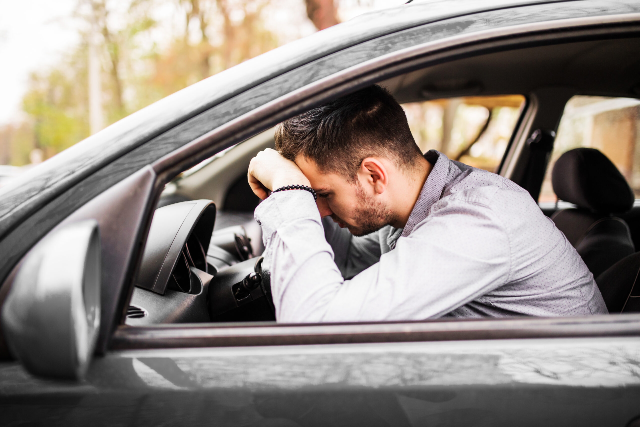 Young man sitting in his car very upset and stressed after hard failure and moving in traffic jam